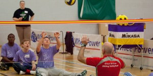 Young adults playing sitting Volleyball