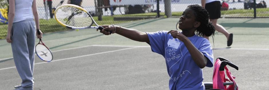 Child playing wheel chair tennis
